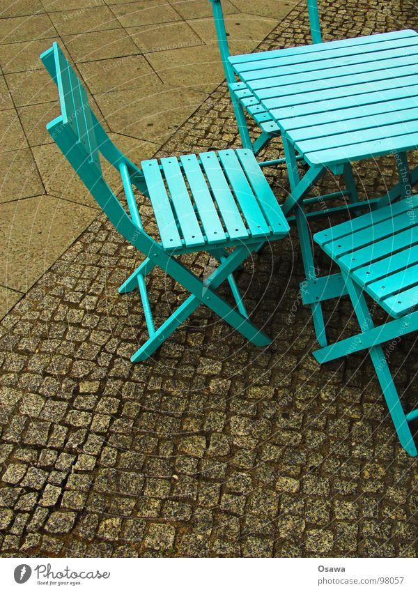 Straßenmöblierung in Cyan grün blau Holz Tisch Stuhl Café Möbel Bürgersteig Verkehrswege Kopfsteinpflaster zyan Pflastersteine Straßencafé Campingstuhl