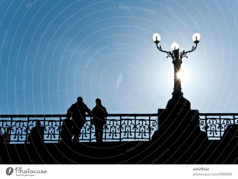 Belgischer Armleuchter III Mensch Paar 3 Wolkenloser Himmel Sonne Sonnenlicht stehen blau schwarz Brücke Brückengeländer Schmiedeeisen Straßenbeleuchtung