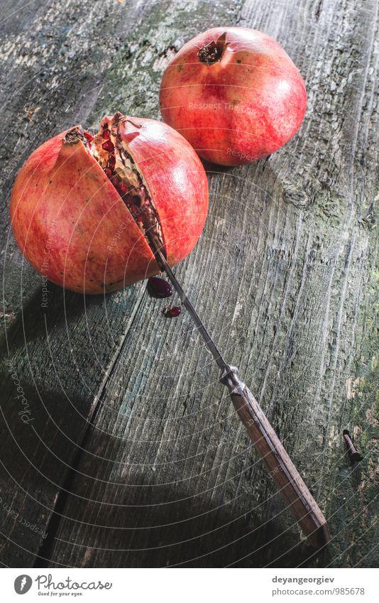Granatapfel auf Holztisch Frucht Essen Vegetarische Ernährung Saft Tisch Natur frisch saftig rot Farbe hölzern Messer reif Hintergrund organisch Gesundheit süß