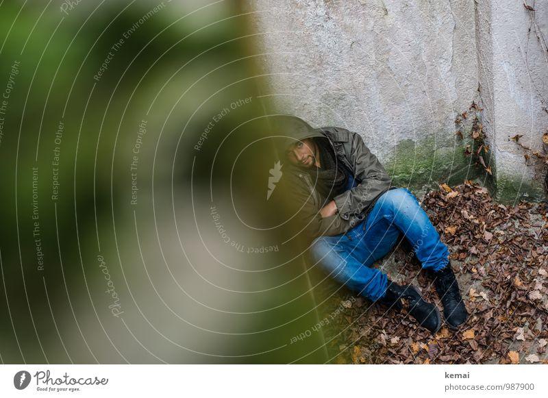 In der Ecke Mensch maskulin Junger Mann Jugendliche Erwachsene Leben Körper 1 18-30 Jahre Herbst Blatt Jeanshose Mantel Stiefel Kapuze liegen sitzen dunkel grün