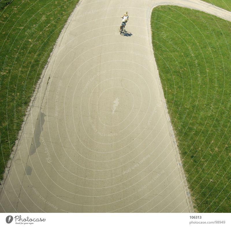 HOCKENHEIM FÜR ARME Frau Fahrrad Fahrradfahren unterwegs Fahrradweg Fahrradtour Straße Kurve Rasen Grünfläche einzeln Vogelperspektive Rückansicht Mobilität