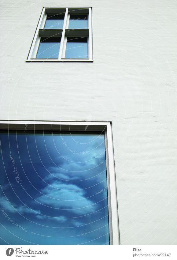 Eine weiße Hauswand mit Fenstern in denen sich blauer Himmel mit Wolken spiegelt Spiegelung Fassade Ausblick Zukunft Architektur Reflexion & Spiegelung Gebäude