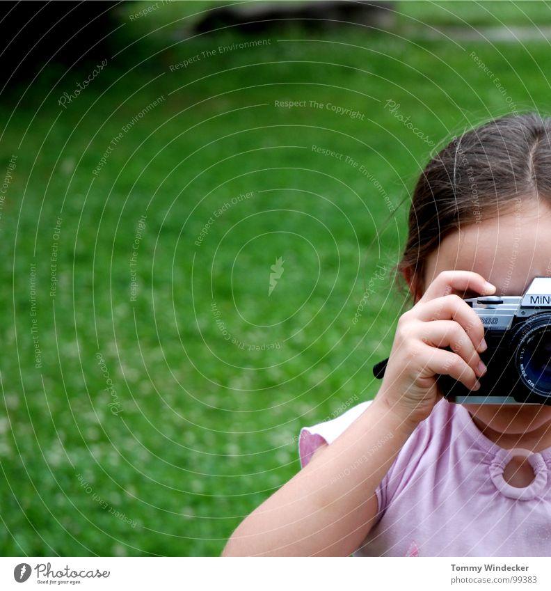 Photogen(e) Mädchen Kind talentiert Fotografie Fotografieren Momentaufnahme Hand Finger Wiese Fotokamera Zopf festhalten filmen analog Körperhaltung Bildung