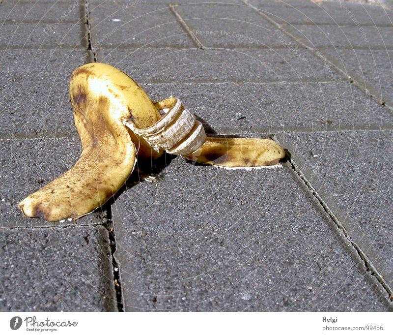 Bananenschale liegt auf einem Gehweg Bürgersteig Fuge grau wegwerfen Müll Biomüll Glätte gelb braun weiß Unfall aufgegessen scheckig Unfallgefahr fallen
