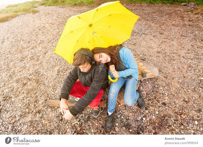 Geschwisterpaar unter einem gelben Regenschirm am Strand Lifestyle Erholung Ausflug Mensch maskulin feminin Paar Jugendliche 2 13-18 Jahre Kind Umwelt Erde