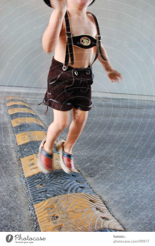 Juchiza Kind Freude Straße Junge springen Beine Fuß laufen Beton Beginn Österreich Erfolg Wachstum Tracht Asphalt stoppen